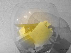 Glas mit gelben Zetteln.