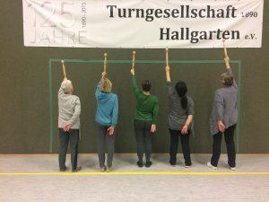 Auf dem Foto sieht man das Logo der Turngesellschaft Hallgarten e.V. und die Kursteilnehmer des IDOGO Kurses