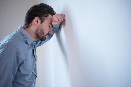 Mann mit Kopf an der Wand, erschöpft. Stress.