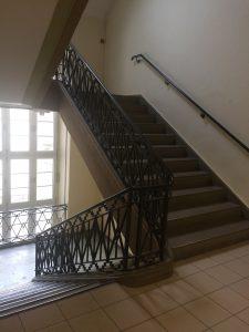 Auf dem Bild sieht man das Treppenhaus mit antikem Geländer im Rheingau Gymnasium