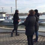 Die Trainerin Pia Forkheim erklärt den Teilnehmern ihre Aufgabe beim Walken, am Rheinufer