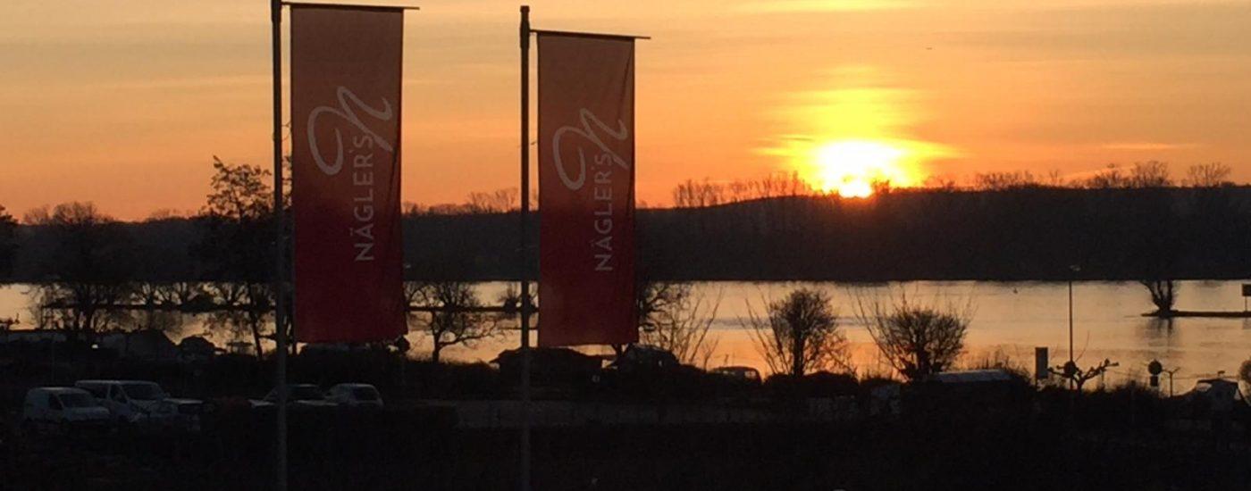 Fahnen vom Hotel Naegler's mit Blick auf den Rhein im Sonnenaufgang