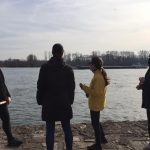 Teilnehmer im Gespräch mit Pia Forkheim und Blick auf den Rhein