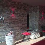 Eingangsbereich im Nägler's Fine Lounge Hotel, Steinwand, Metallstühle, Sessel, Kerzenleucher, Pink