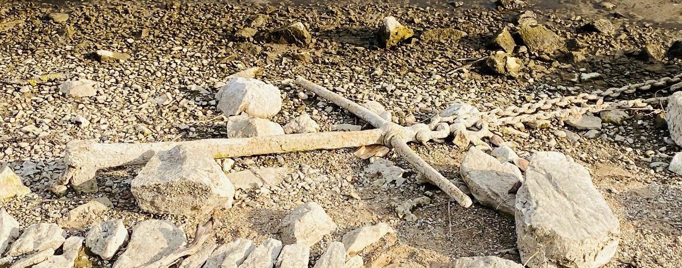 Ein Anker im trockenen Sand.